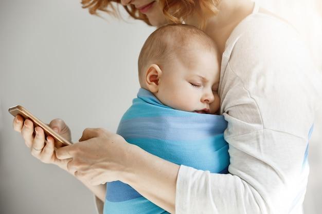 Bela jovem mãe lê artigos sobre a vida de maternidade no telefone enquanto adorável filho dormindo no peito no sling azul bebê. Foto gratuita