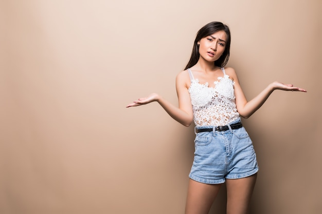 Bela jovem mulher asiática, apresentando seu produto muito emocionante, isolado na parede bege Foto gratuita