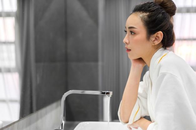 Bela jovem mulher asiática lavando o rosto limpo com água e sorrindo em frente ao espelho no banheiro. beleza e spa. pele fresca perfeita Foto Premium