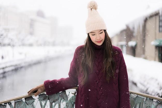 Bela jovem mulher asiática sorrir e feliz com viagem de viagem no canal otaru hokkaido japão Foto gratuita