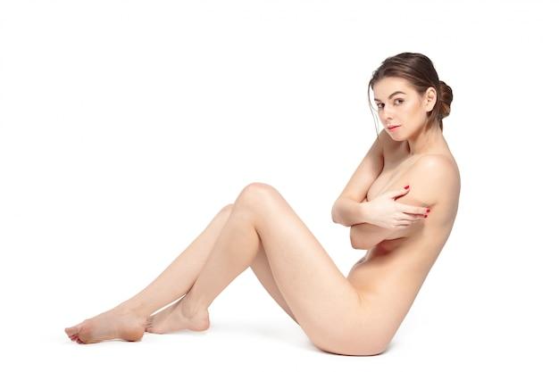 Bela jovem mulher nua morena deitada Foto Premium