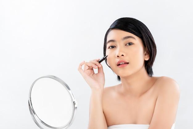 Bela jovem pele radiante mulher asiática segurando a maquiagem delineador Foto Premium