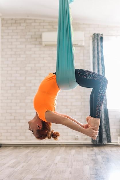 Bela jovem pendurado de cabeça para baixo enquanto pratica ioga aérea Foto gratuita