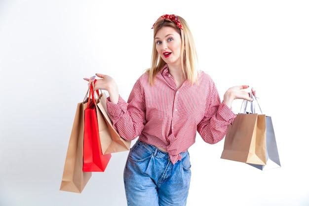 Bela jovem pin-up de camisa quadriculada e bandana segurando sacolas de compras no fundo da parede branca. Foto Premium