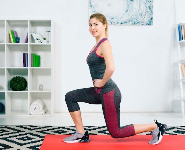 Bela jovem praticando ioga em casa Foto gratuita