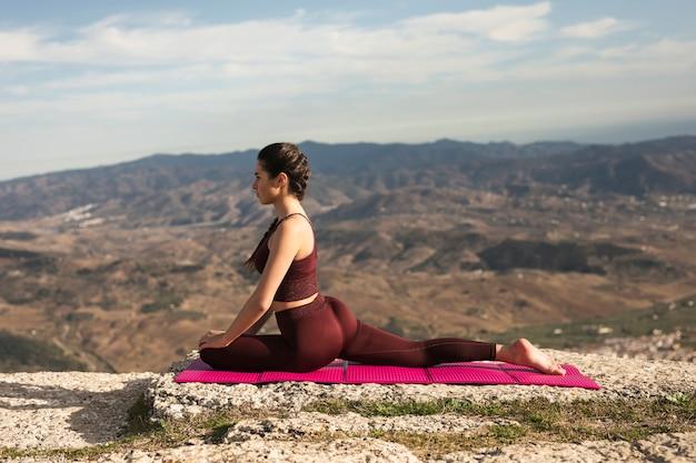 Bela jovem praticando ioga Foto gratuita