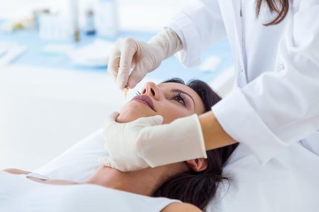 Bela jovem recebendo injeção cosmética botox no rosto dela. Foto gratuita