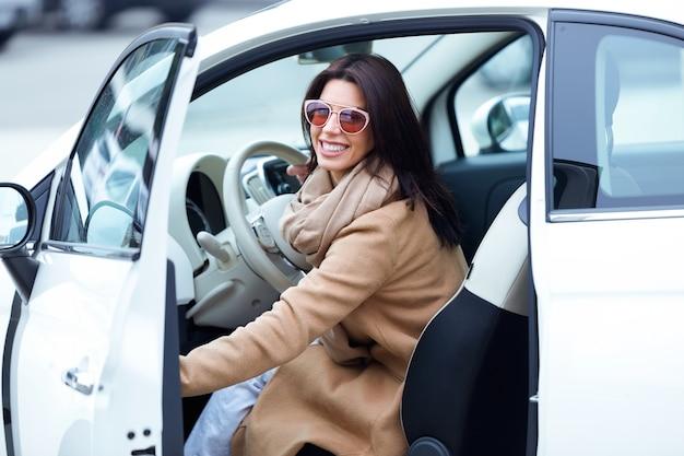 Bela jovem sai do carro. Foto Premium