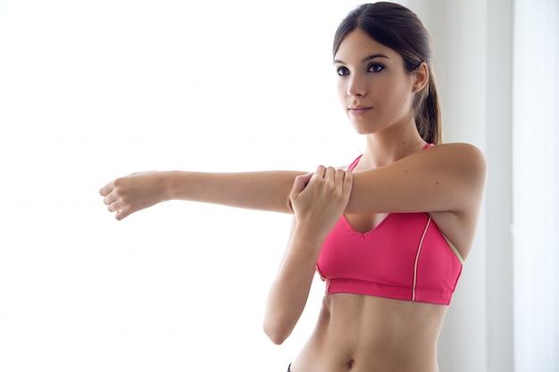 Bela jovem saudável fazendo exercícios em casa. Foto gratuita