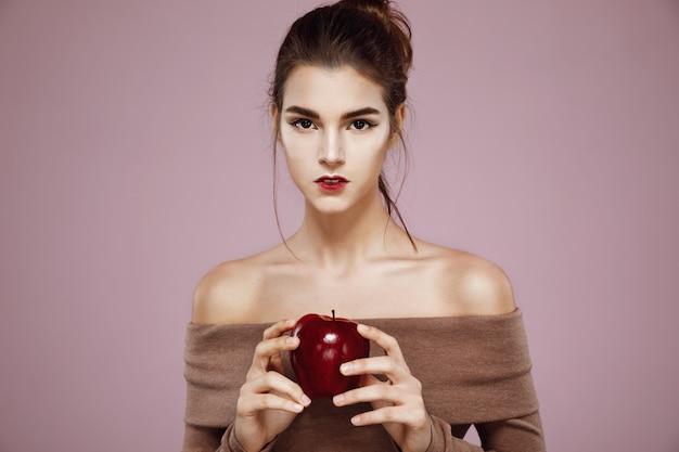 Bela jovem segurando a maçã vermelha nas mãos. Foto gratuita