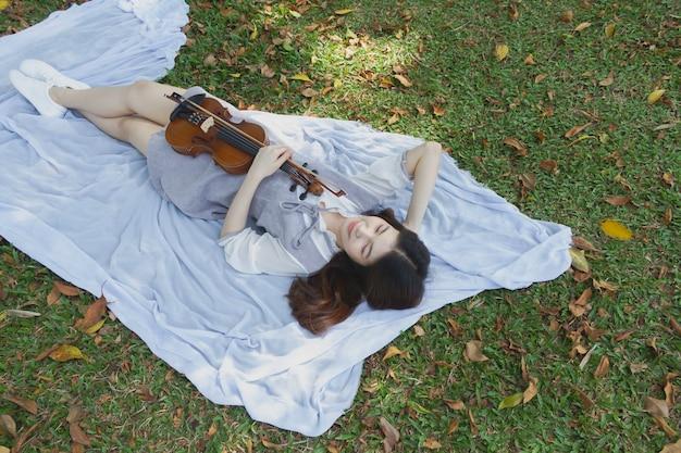 Bela jovem segurando a mão de violino e bowin, deitada em um piso verde com sensação de relaxamento, em um parque Foto Premium