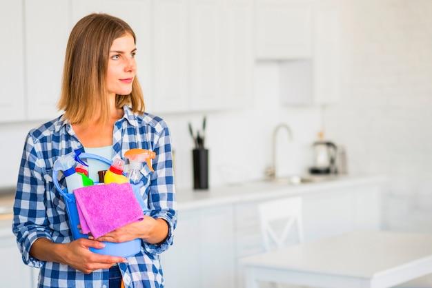 Bela jovem segurando equipamentos de limpeza no balde Foto gratuita