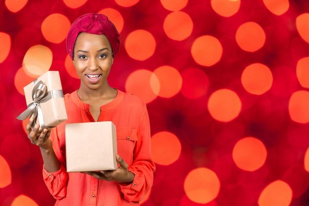 Bela jovem segurando um presente Foto Premium