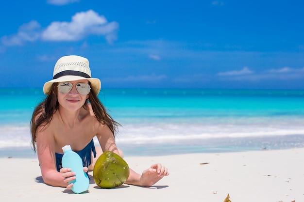 Bela jovem segurando um suncream deitado na praia tropical Foto Premium
