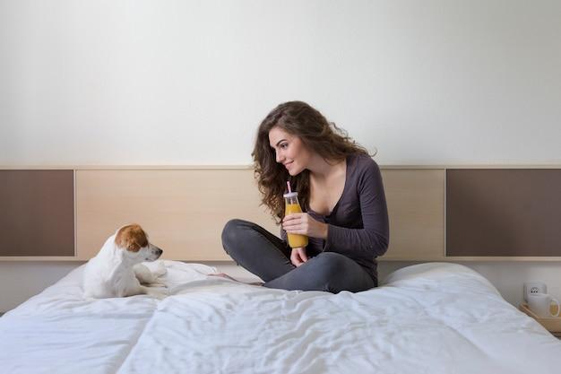 Bela jovem sentada na cama com seu cachorro pequeno bonito além. Foto Premium