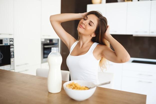Bela jovem sentada na mesa de jantar com sono sonhador enquanto tomando café da manhã Foto gratuita