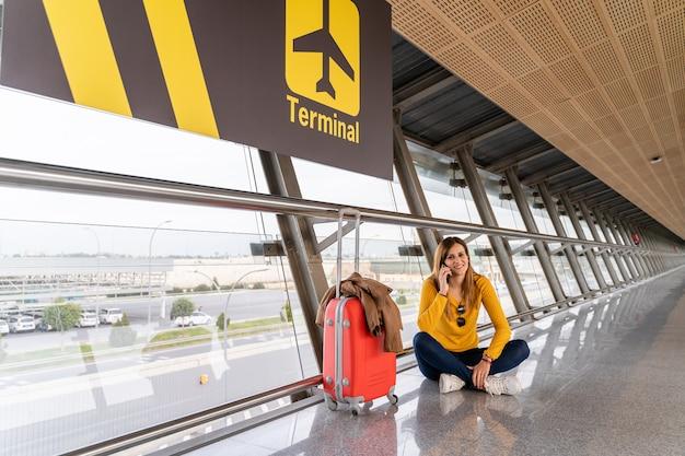 Bela jovem sentada no chão esperando no aeroporto com sua bagagem Foto Premium