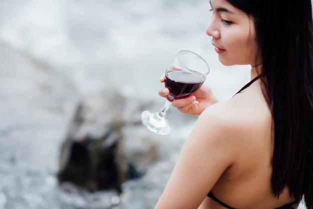 Bela jovem sentada no cocktail beber ao ar livre e ver o rio Foto gratuita