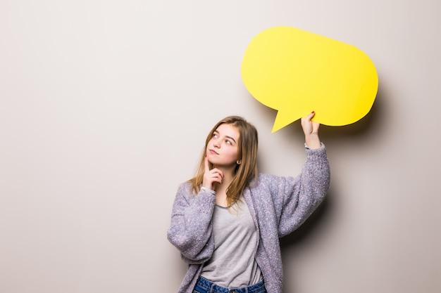Bela jovem sonhadora segurando uma bolha amarela para texto, isolada Foto gratuita