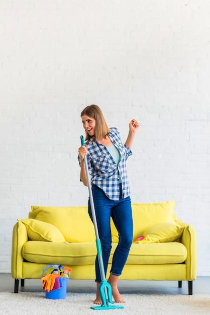 Bela jovem sorridente, limpando a casa cantando Foto gratuita