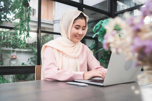 Bela jovem sorridente mulher muçulmana asiática trabalhando no laptop sentado na sala de estar em casa Foto gratuita