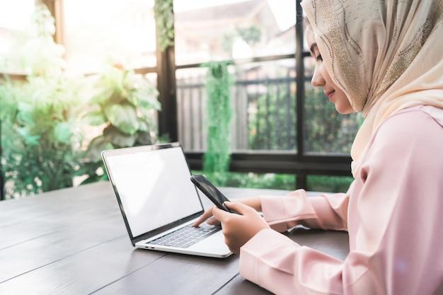 Bela jovem sorridente mulher muçulmana asiática trabalhando no telefone sentado na sala de estar em casa Foto gratuita