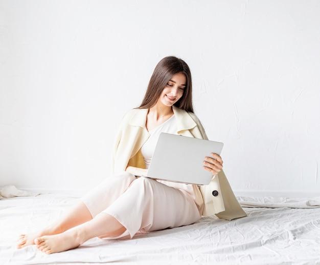 Bela jovem sorridente, sentada no chão e fazendo um projeto freelance no laptop, usando o computador Foto Premium