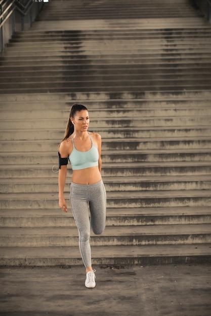 Bela jovem tendo exercício no ambiente urbano Foto Premium