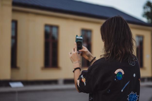 Bela jovem tirando fotos em um smartphone Foto gratuita