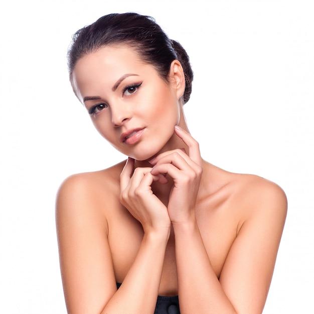 Bela jovem tocando seu rosto Foto Premium