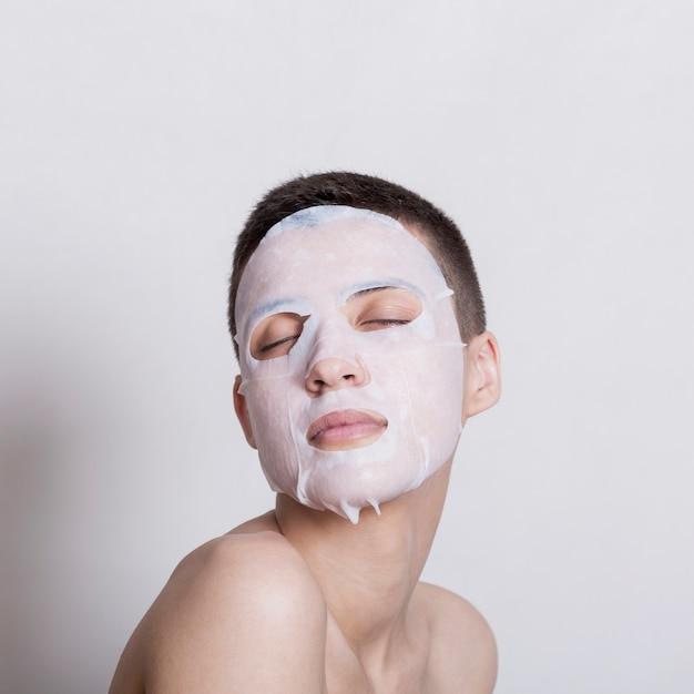 Bela jovem usando máscara facial Foto gratuita