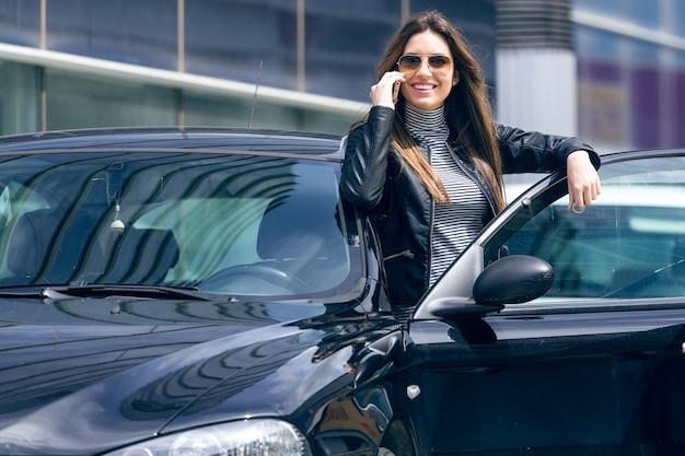 Bela jovem usando seu celular no carro. Foto gratuita