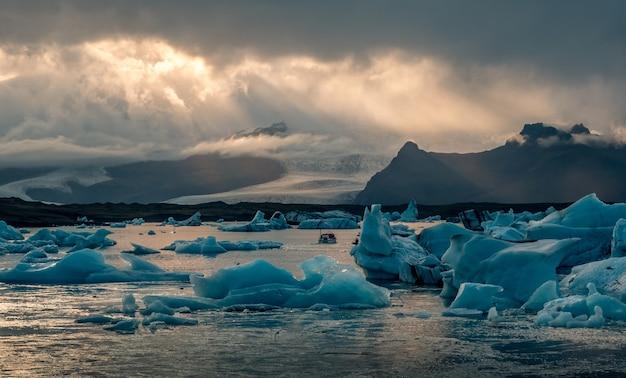 Bela lagoa da geleira jokulsarlon na islândia, com raios de sol em um céu escuro e nublado Foto gratuita