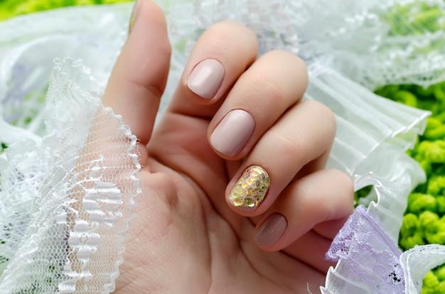 Bela mão feminina com design de unha bege. Foto Premium