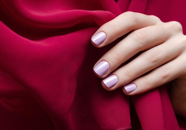 Bela mão feminina com design de unha roxa clara. Foto Premium