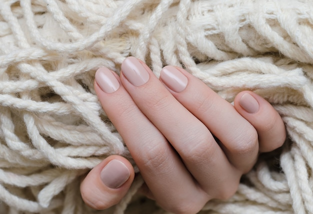Bela mão feminina com design de unhas bege Foto Premium