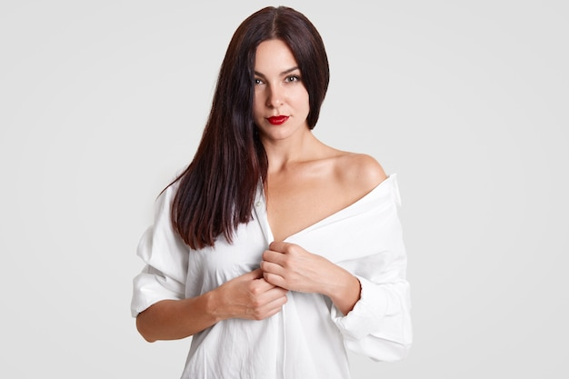 Bela moça com perfeita pele limpa, tem batom vermelho, veste camisa branca solta, mostra ombro nu, flertando. Foto Premium