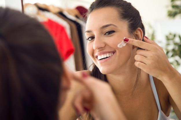 Bela moça cuidando da pele perto do espelho no banheiro. Foto gratuita