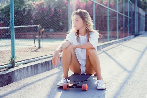 Bela moça sexy em calções com longboard em clima ensolarado Foto gratuita