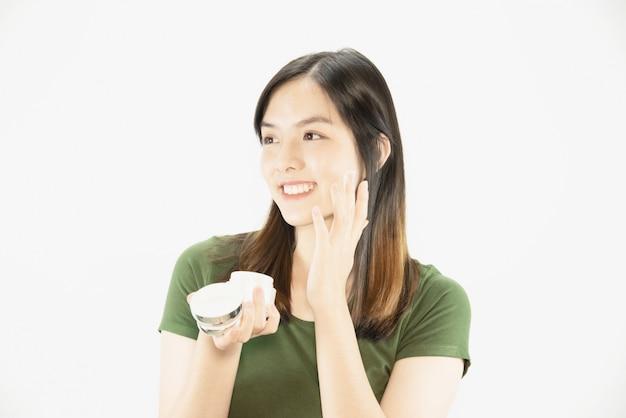 Bela moça usando creme hidratante para cuidados com a pele rosto - mulher e cosmética maquiagem rosto beleza conceito de cuidados da pele Foto gratuita
