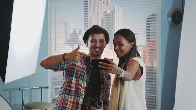 Bela modelo africana fazendo selfie com belo fotógrafo em sessão de fotos em estúdio profissional Foto Premium
