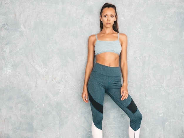 Bela modelo com corpo bronzeado perfeito. feminino posando no estúdio perto da parede cinza Foto gratuita