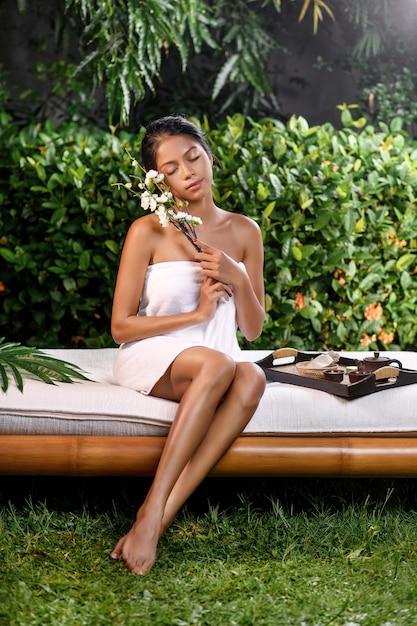 Bela modelo interracial posando com um raminho de flores brancas perto do rosto em uma toalha de terry em um sofá de massagem em que fica uma bandeja para terapia de spa Foto Premium