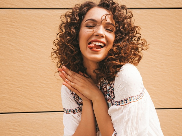 Bela modelo sorridente com afro cachos penteado vestido com vestido branco hipster de verão. Foto gratuita