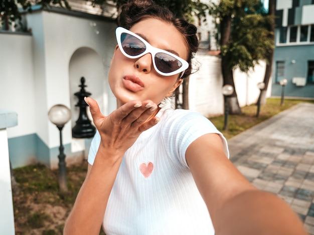 Bela modelo sorridente com penteado de chifres, vestido com roupas casuais de verão. garota despreocupada sexy posando na rua em óculos de sol. tirando fotos de auto-retrato selfie no smartphone. dando beijo de ar Foto gratuita