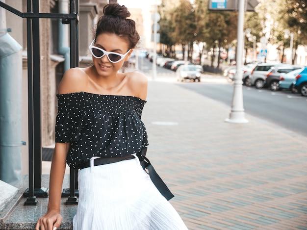 Bela modelo sorridente, vestida com roupas de verão elegante. garota despreocupada sexy sentada na rua. empresária moderna na moda em óculos de sol se divertindo Foto gratuita