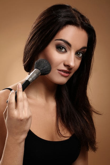 Bela morena com pincel de maquiagem Foto gratuita