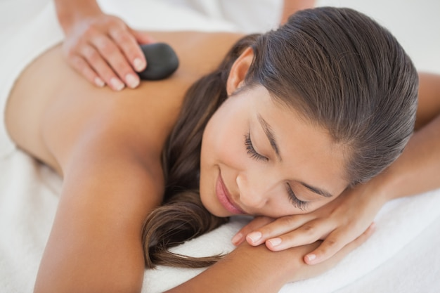 Bela morena desfrutando de uma massagem com pedras quentes Foto Premium