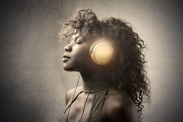 Bela mulher afro ouvindo música Foto Premium