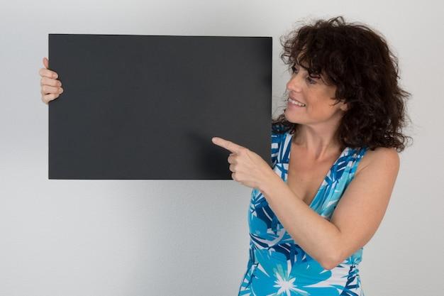 Bela mulher, apontando para o cartaz preto em branco Foto Premium